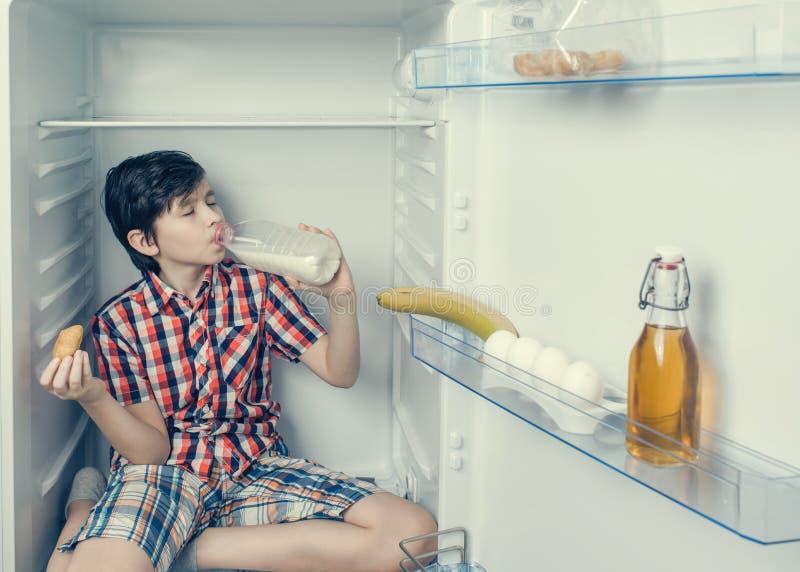 En pojke i en skjorta och kortslutningar som äter en giffel och en drink, mjölkar inom en kyl med mat och produkten Närbild arkivbilder