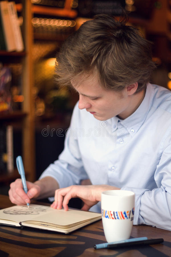 En pojke i skjortateckning i anteckningsboken arkivbild