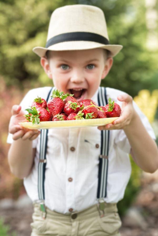 En pojke i en sugrörhatt äter mogna doftande jordgubbar royaltyfri fotografi