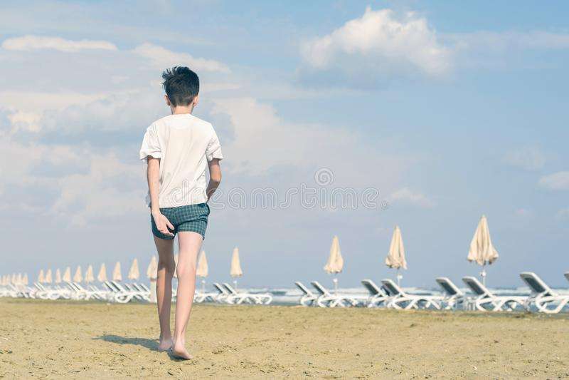 En pojke i en T-tr?ja och kortslutningar g?r p? den sandiga Mackenzie stranden i Larnaca cyprus royaltyfri foto