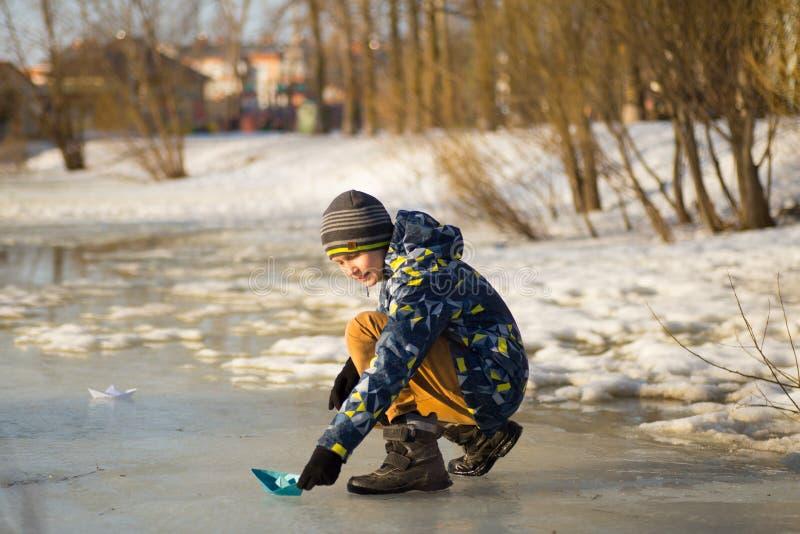 En pojke lanserar en pappers- liten vik för fartyg på våren royaltyfri bild