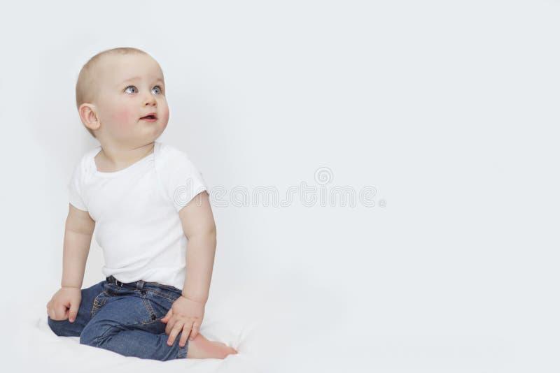 En pojke med blåa ögon i jeans på en vit bakgrund royaltyfri bild