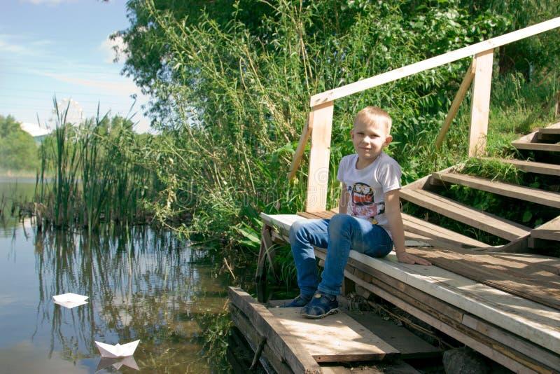 En pojke med ett pappers- fartyg vid floden royaltyfria bilder