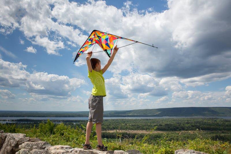 En pojke med en färgrik drake i hans händer mot den blåa himlen med moln Ett barn i en gul T-tröja och kortslutningar h?rligt arkivfoton