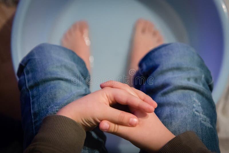 En pojke med fingrar korsade händerna och sminkade sig hemma och sminkade fötterna i varmt saltvatten i plasttvättskålen. arkivfoto