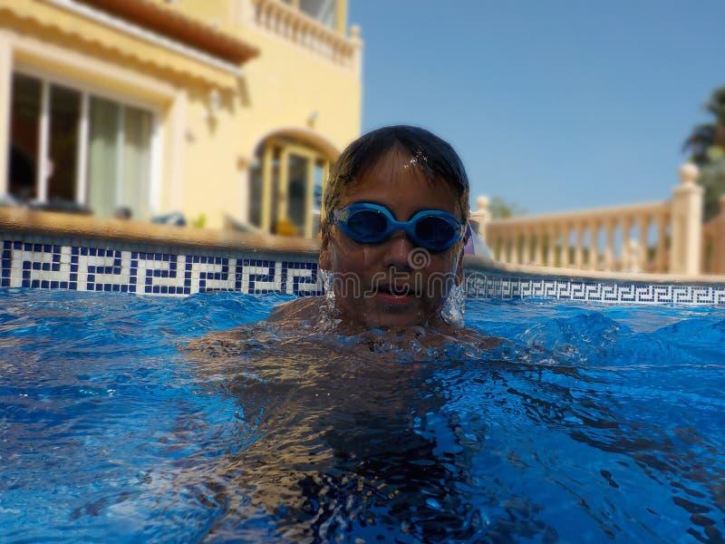 En pojke med a googlar simning i en simbassäng arkivfoton