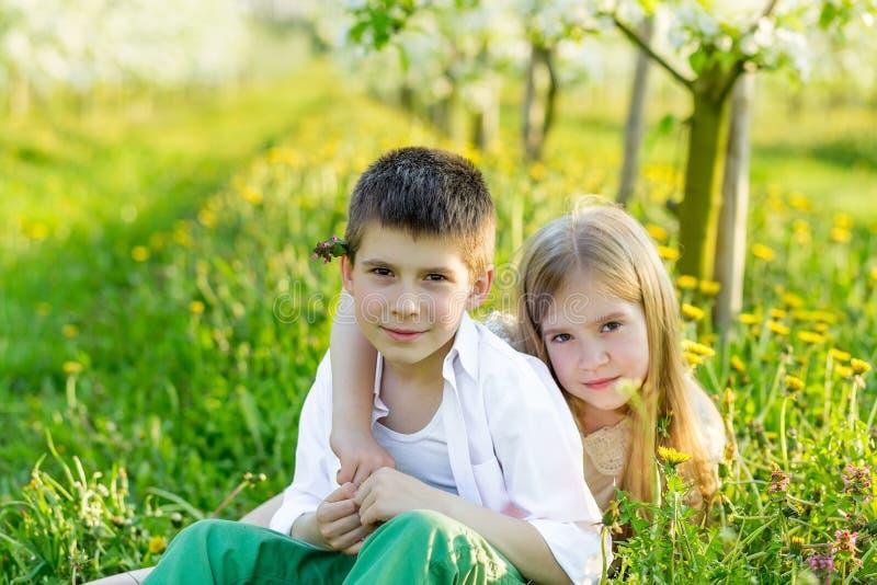 En pojke och en flicka vilar i en blommande trädgård på våren royaltyfri foto