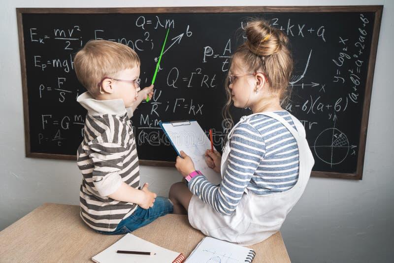 En pojke och en flicka sitter på ett skolaskrivbord och studerar formler på kritabrädet royaltyfria bilder