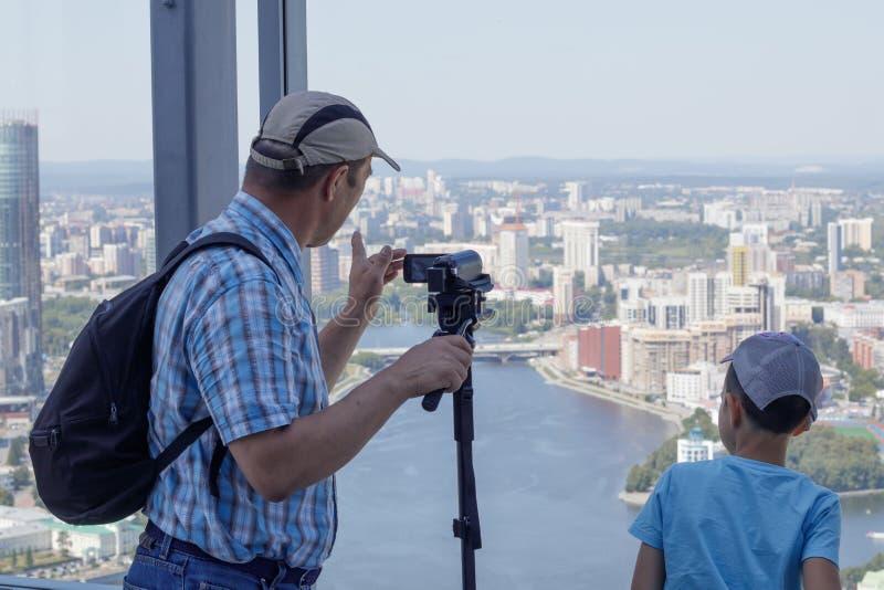 En pojke och hans farfar står på det panorama- fönstret av ett höghus som ser staden av Yekaterinburg royaltyfri fotografi