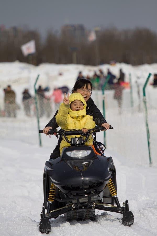 En pojke och hans moder rider en snömotorcykel