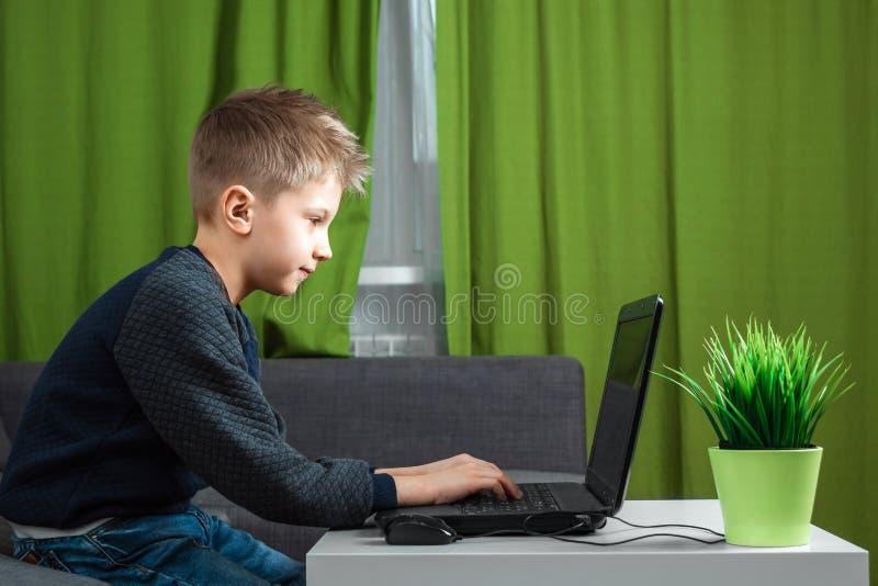 En pojke på en bärbar dator spelar lekar eller håller ögonen på en video Begreppet av böjelse till dataspelar, suddig vision, men royaltyfria bilder