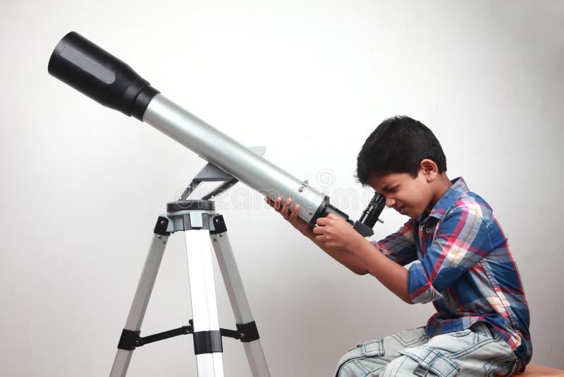 En pojke ser till och med ett teleskop royaltyfri bild