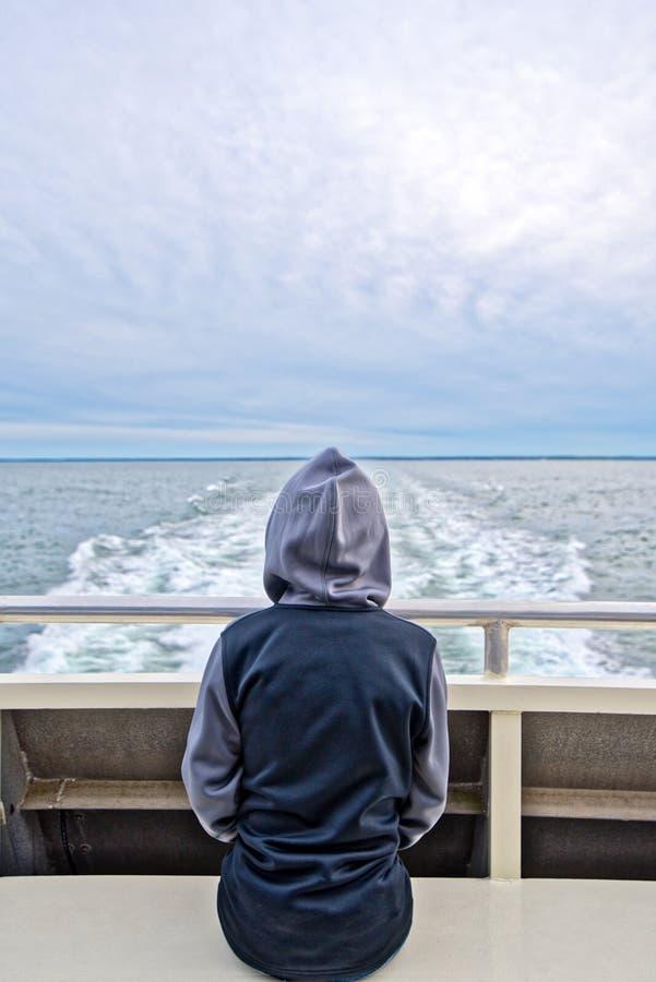 En pojke sitter baktill av ett fartyg och håller ögonen på ön av Nantucket att försvinna från horisonten arkivfoto