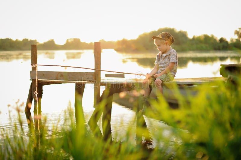 En pojke sitter runt om brasan vid floden på natten arkivfoto