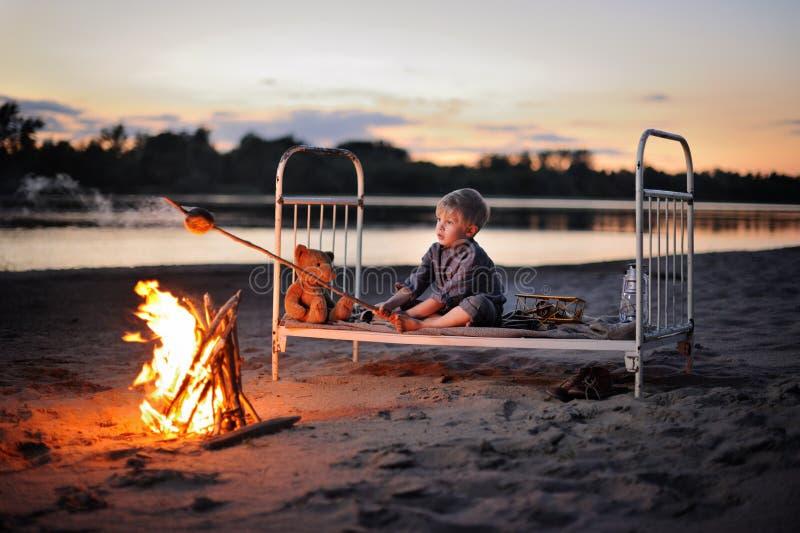En pojke sitter runt om brasan vid floden på natten fotografering för bildbyråer