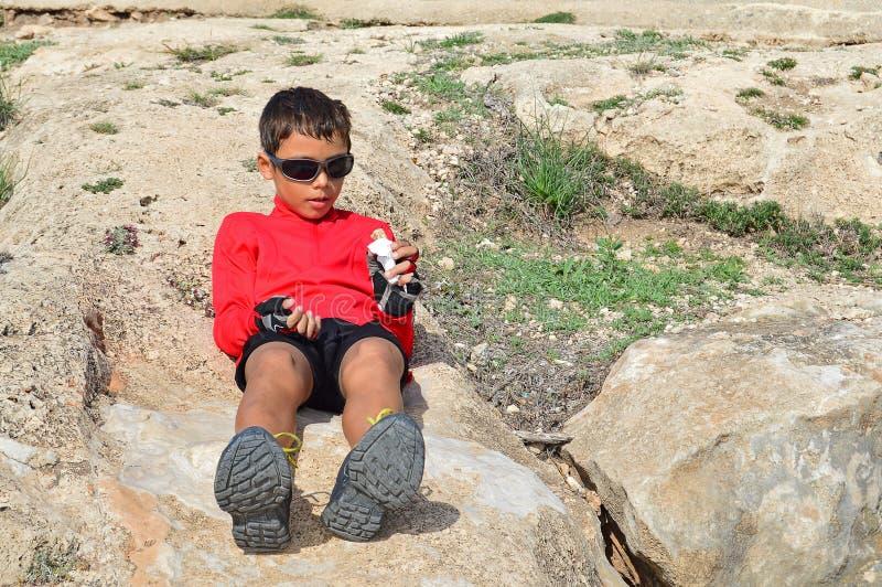En pojke som äter på, vaggar arkivfoton