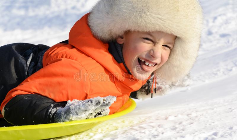 En pojke som ler att lägga på hans släde, närbildstående körning av rolig pulkavinter arkivfoto
