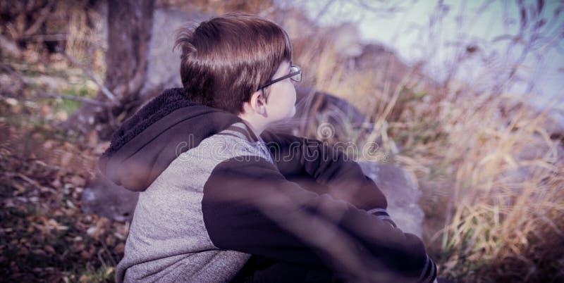 En pojke som sitter på dagdrömma för bank royaltyfri foto
