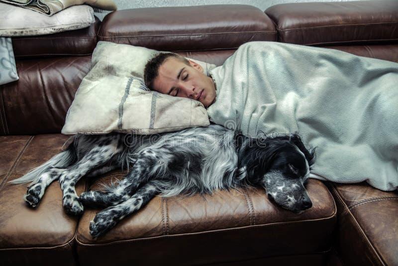 En pojke som sover med hans hund arkivfoto