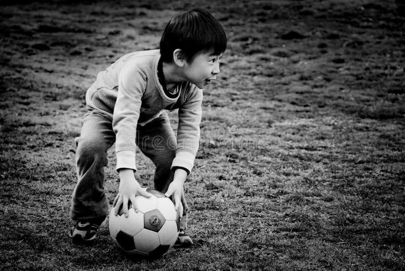 En pojke som spelar fotboll på parkera arkivbilder