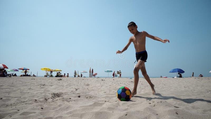 En pojke som spelar fotbollfotboll som kör med en boll på sand på stranden royaltyfria foton
