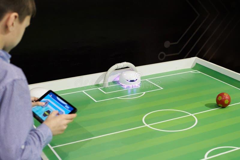 En pojke som spelar tabellfotboll med en röd boll med en robot på ett G arkivbilder