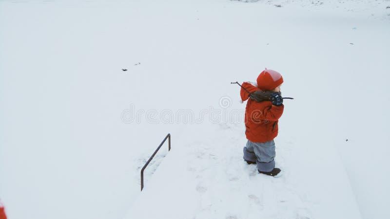 En pojke som undersöker ett djupfryst damm arkivbilder