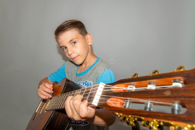 En pojke spelar gitarren på en grå bakgrund i studion, brett vinkelnärbildfoto royaltyfri foto
