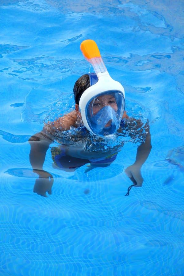 En pojke spelar i en simbassäng med den Easybreath maskeringen arkivbilder