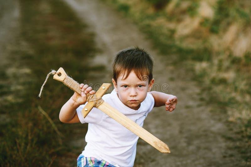 En pojke spelar med ett träsvärd royaltyfria bilder