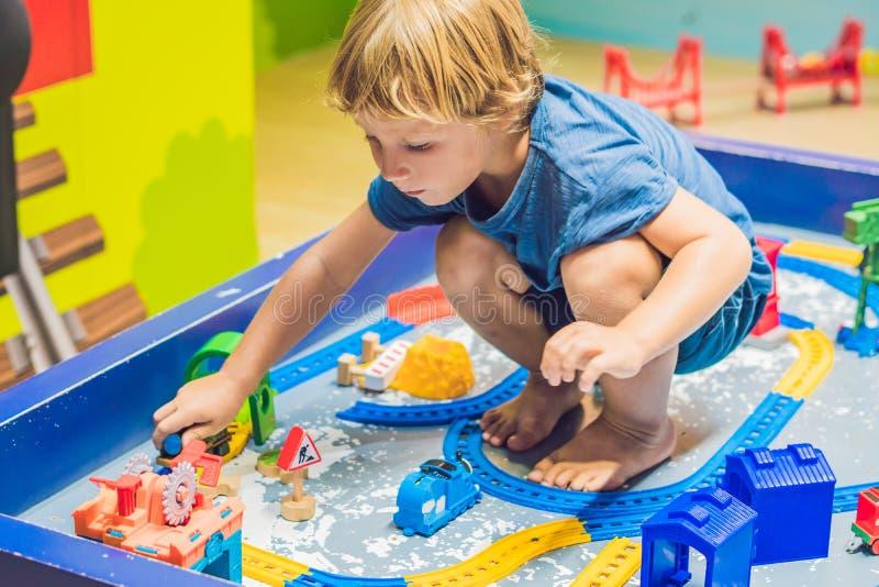 En pojke spelar med en leksakjärnväg royaltyfria foton