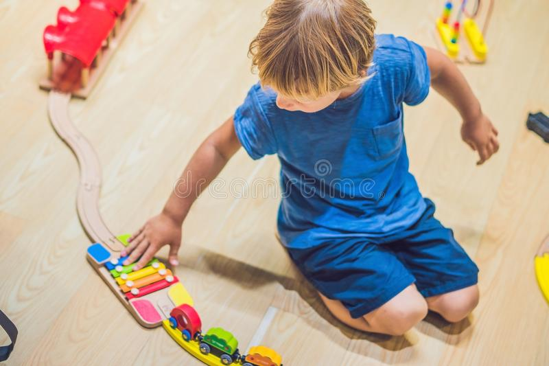 En pojke spelar med en leksakjärnväg royaltyfria bilder