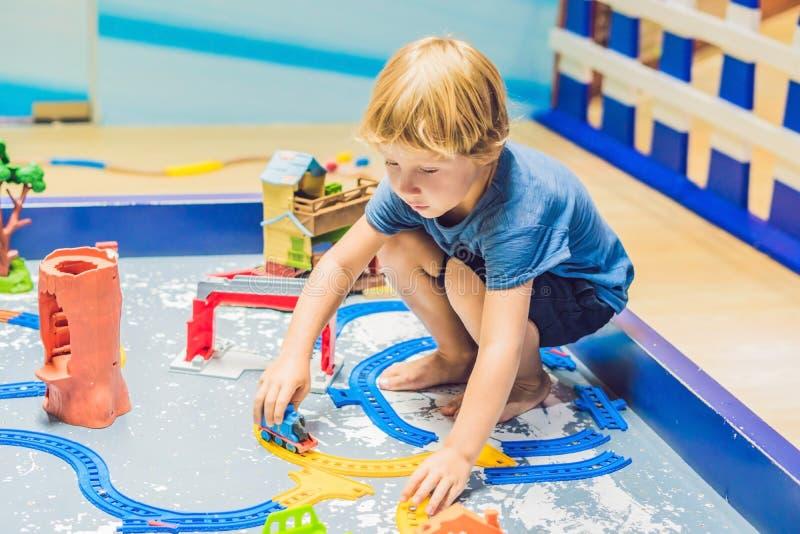En pojke spelar med en leksakjärnväg arkivfoto