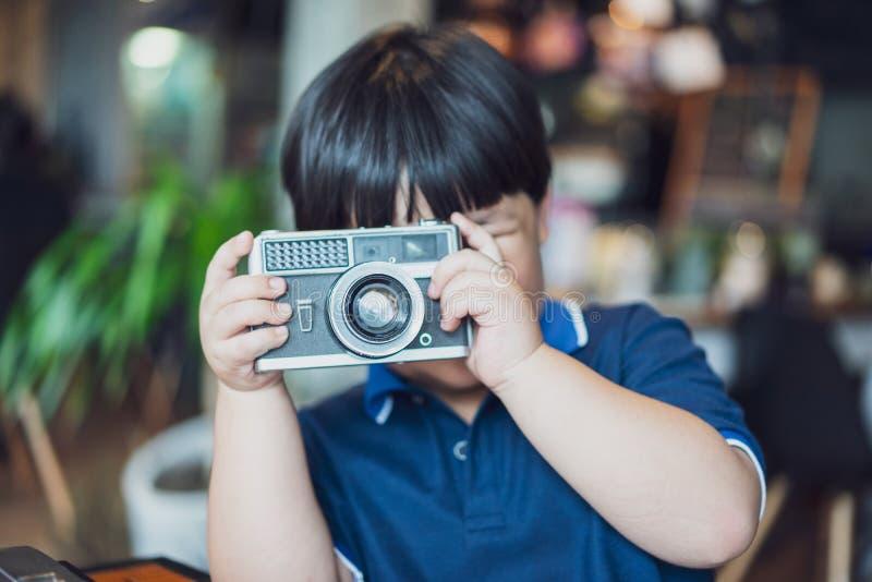 En pojke tar en fotofilmkamera royaltyfria foton