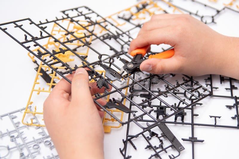 En pojkes hand som monterar plast- modeller genom att använda hjälpmedel arkivfoto
