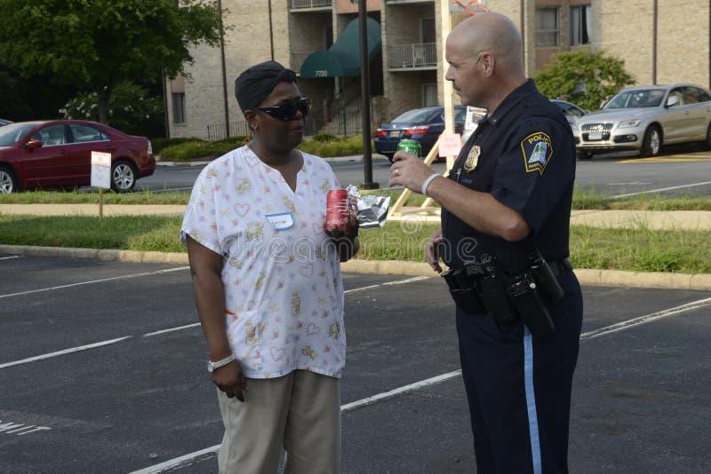 En polis talar till en afrikansk amerikan på händelser för en gemenskap royaltyfria bilder