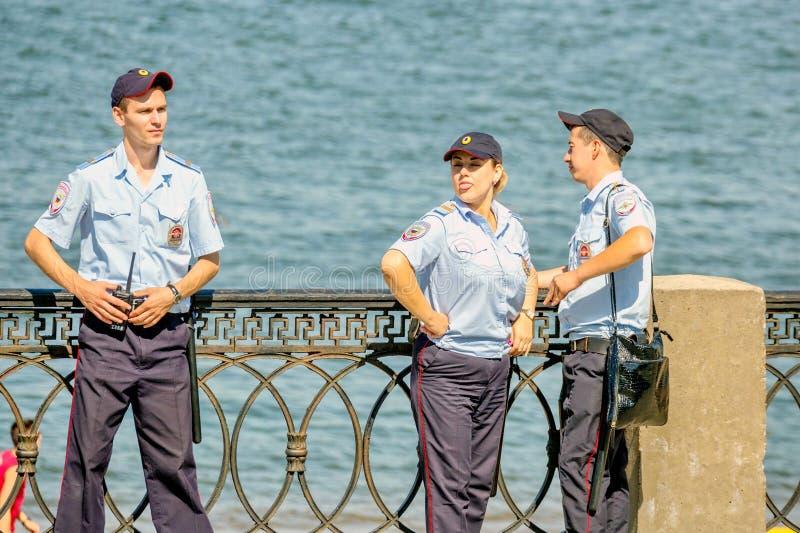En polispatrull observerar beställning under en ferie på den Volga River invallningen på en varm dag för sommar royaltyfri fotografi