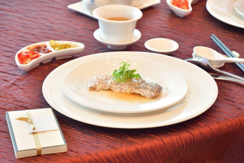 En portion av en skiva av fiskkött på en platta på en restaurang arkivbild