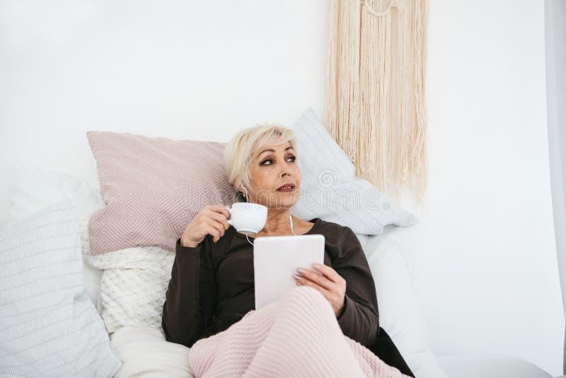 En positiv kvinna dricker ett morgonkaffe som ligger i säng och, använder en minnestavla för att hålla ögonen på video, lyssna ti arkivfoton