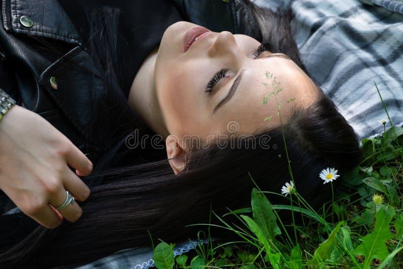 En positiv kvinna som ner ligger på en filt i ängen på solig dag för vår och ser upp royaltyfri foto