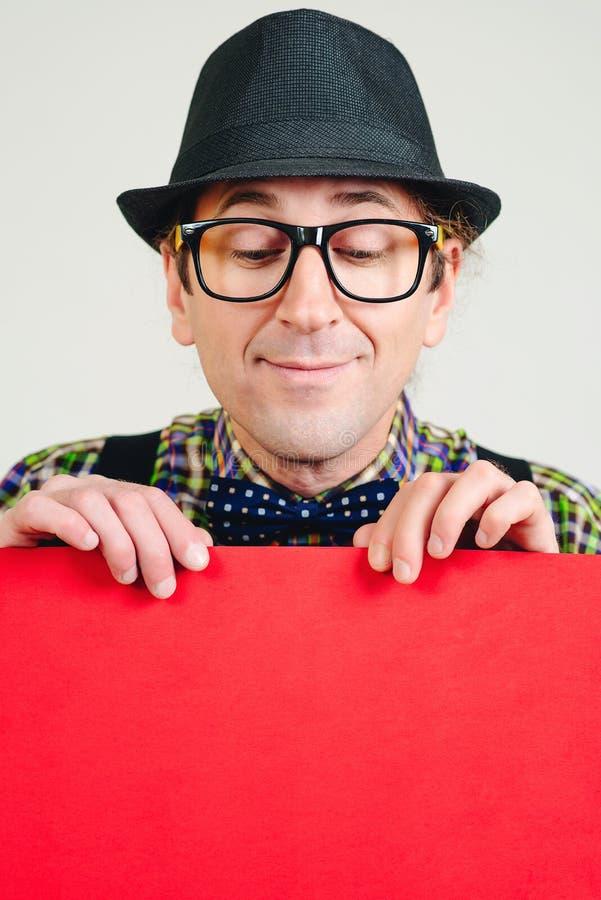 En positiv nörd håller ett meddelande på banderollen Människan visar utrymme för din design Han har glasögon, retrohatt och skjor arkivfoton