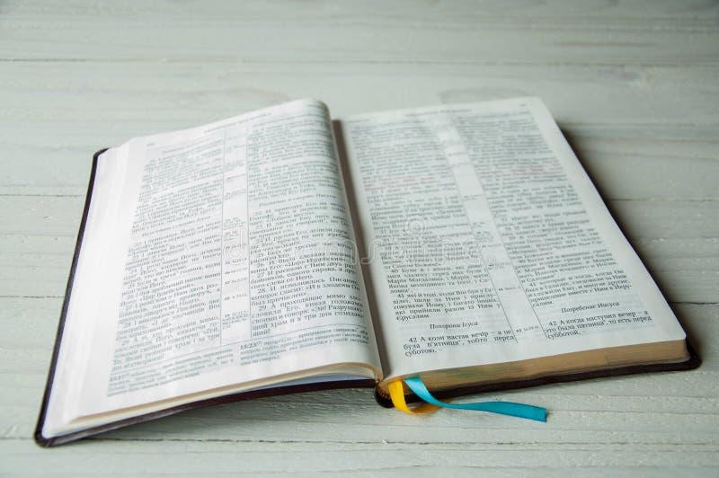 En ?ppen bok p? en tr?tabell Bibel på träbakgrund arkivbilder