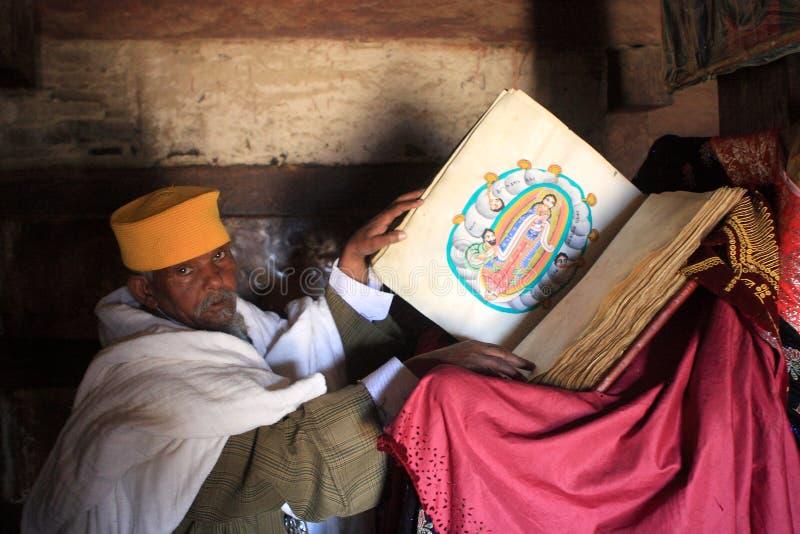 En präst Displays Sacred Illustrations från en helig bok arkivbilder