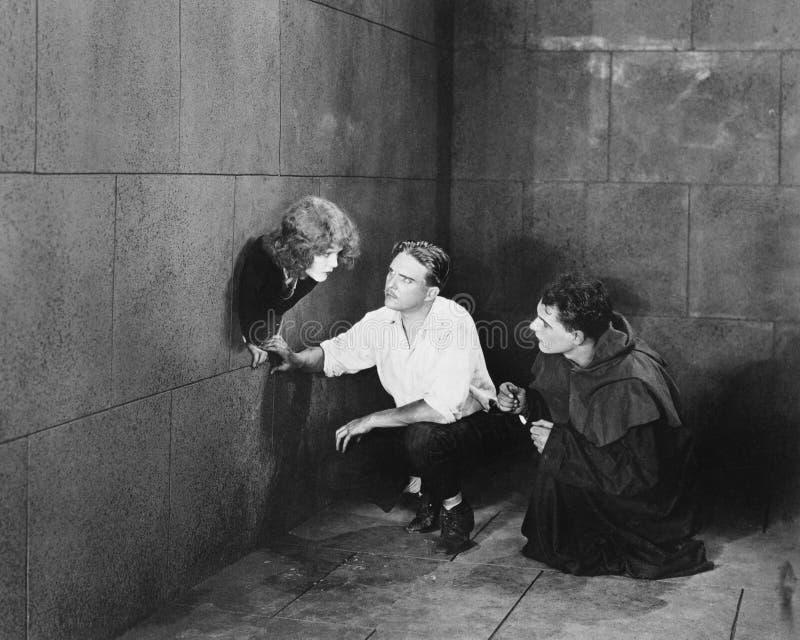 En präst och en man som försöker att hjälpa en ung kvinna att fly (alla visade personer inte är längre uppehälle, och inget gods  royaltyfria foton