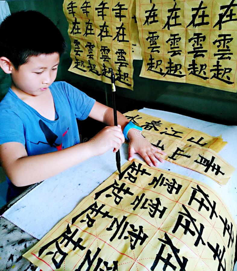 En praktiserande kinesisk kalligrafi för barn försiktigt royaltyfri foto
