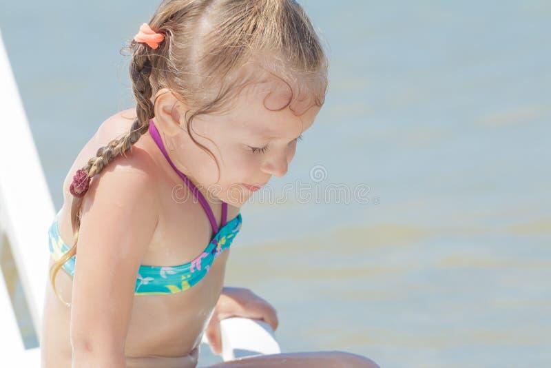En prenant un bain de soleil la petite fille badinez sur la chaise de plage en plastique blanche photo stock