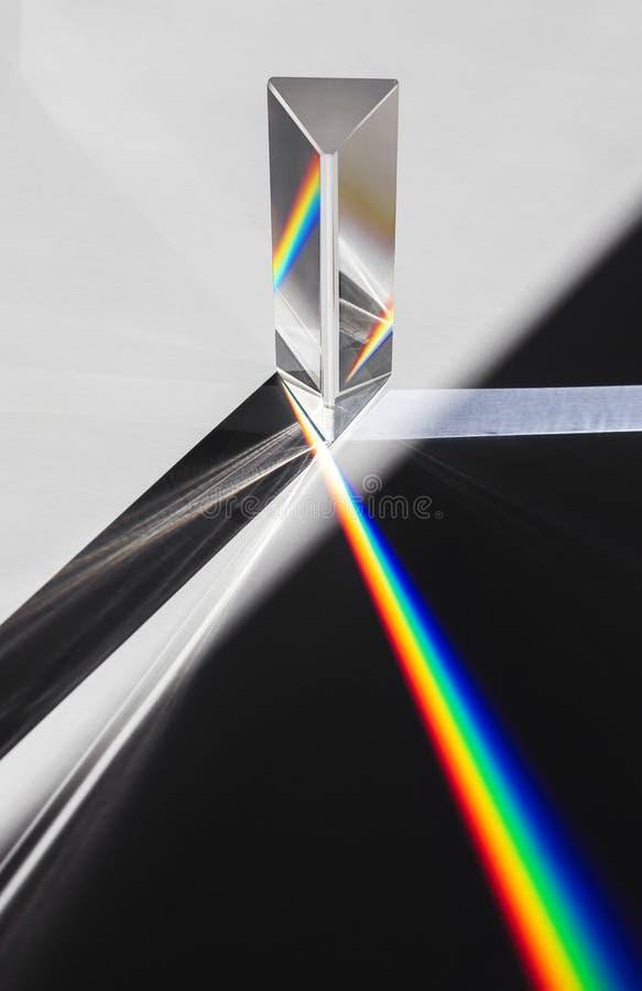 En prisma som skingrar solljus som delar in i ett spektrum på en vit bakgrund fotografering för bildbyråer