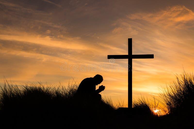 En puesta del sol de la cruz del rezo imágenes de archivo libres de regalías
