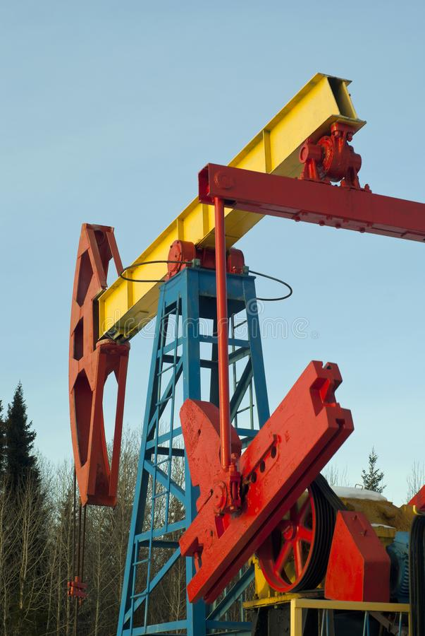 En pumpjack över ett olje- väl i ett skogsbevuxet landskap för vinter royaltyfri bild