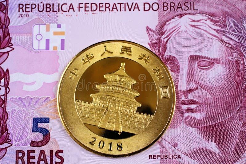 En purpurfärgad fem brasiliansk reais sedel med ett kinesiskt ett guld- mynt för uns arkivbild